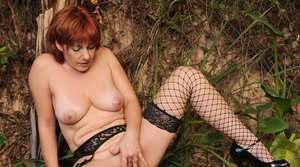 Aged redhead removes her black lingerie to model in mesh stockings